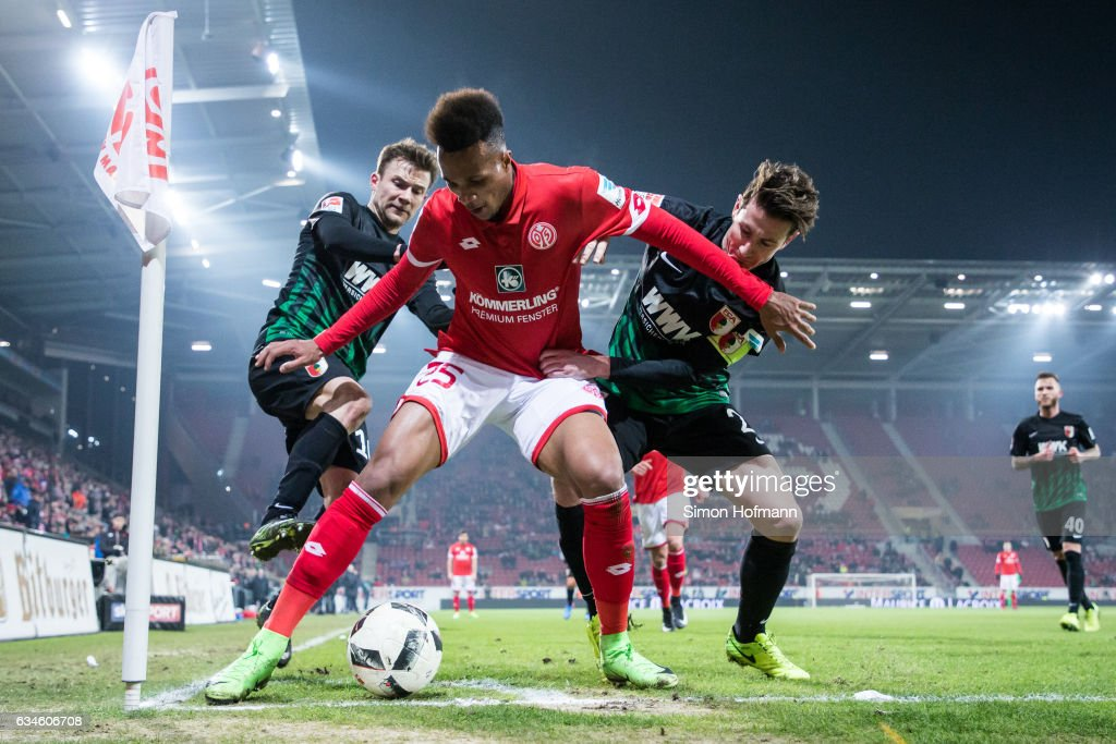 Jean-Philippe Gbamin of Mainz is challenged by Paul Verhaegh and Daniel Baier (L) of Augsburg during the Bundesliga match between 1. FSV Mainz 05 and FC Augsburg at Opel Arena on February 10, 2017 in Mainz, Germany.