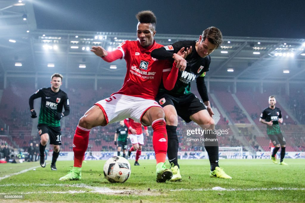 Jean-Philippe Gbamin of Mainz is challenged by Paul Verhaegh of Augsburg during the Bundesliga match between 1. FSV Mainz 05 and FC Augsburg at Opel Arena on February 10, 2017 in Mainz, Germany.