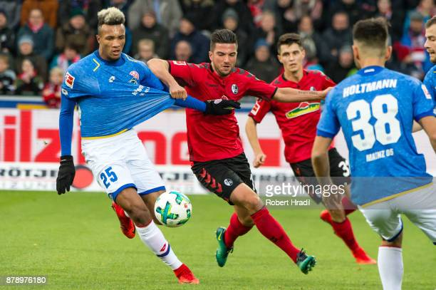 JeanPhilippe Gbamin of Mainz vies with Marco Terrazzino of Freiburg during the Bundesliga match between SportClub Freiburg and 1 FSV Mainz 05 at...