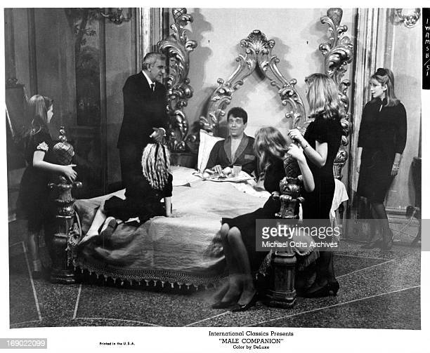 JeanPierre Cassel sitting up in bed as Adolfo Celi and five females stand at his side in a scene from the film 'Male Companion' 1964