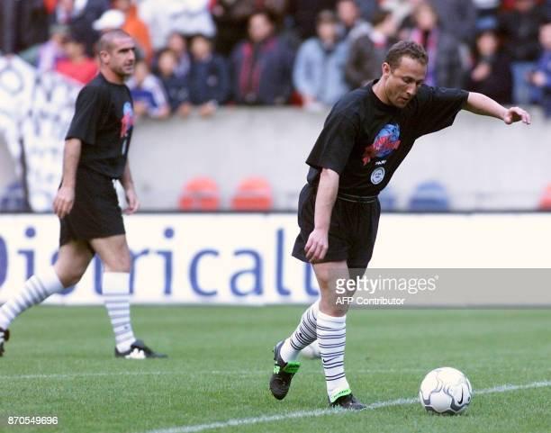 JeanPierre Papin et Eric Cantona évoluent sur la pelouse du Parc des Princes à Paris le 21 mai 2000 lors du jubilé du footballeur Laurent Fournier...