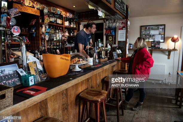 Jean-Pierre Robinet , owner of The Old Forge, serves a customer a the bar in his pub in Inverie on the Knoydart peninsular in the Scottish Highlands...
