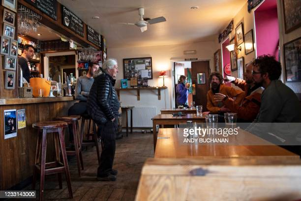 Jean-Pierre Robinet , owner of The Old Forge, serves customers in his pub in Inverie on the Knoydart peninsular in the Scottish Highlands on May 21,...