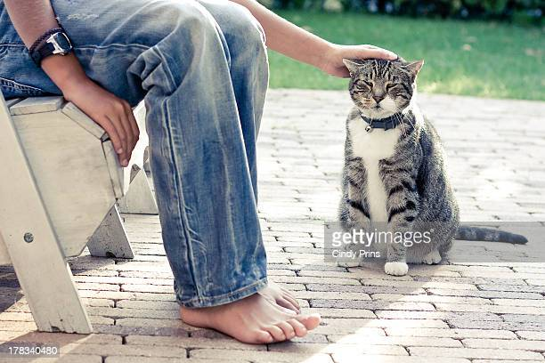 Jeans and bare feet and a hand petting a cat