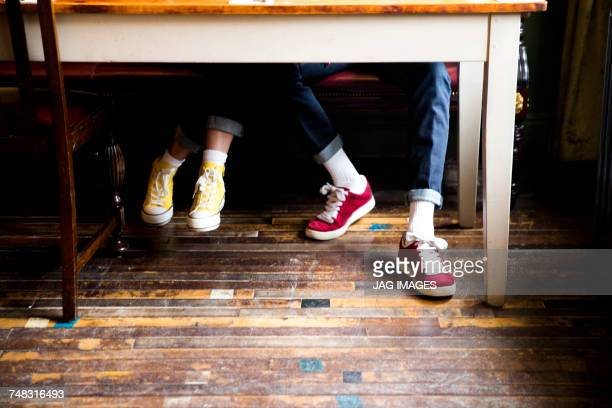 Jeans and trainers worn by couple sitting at table