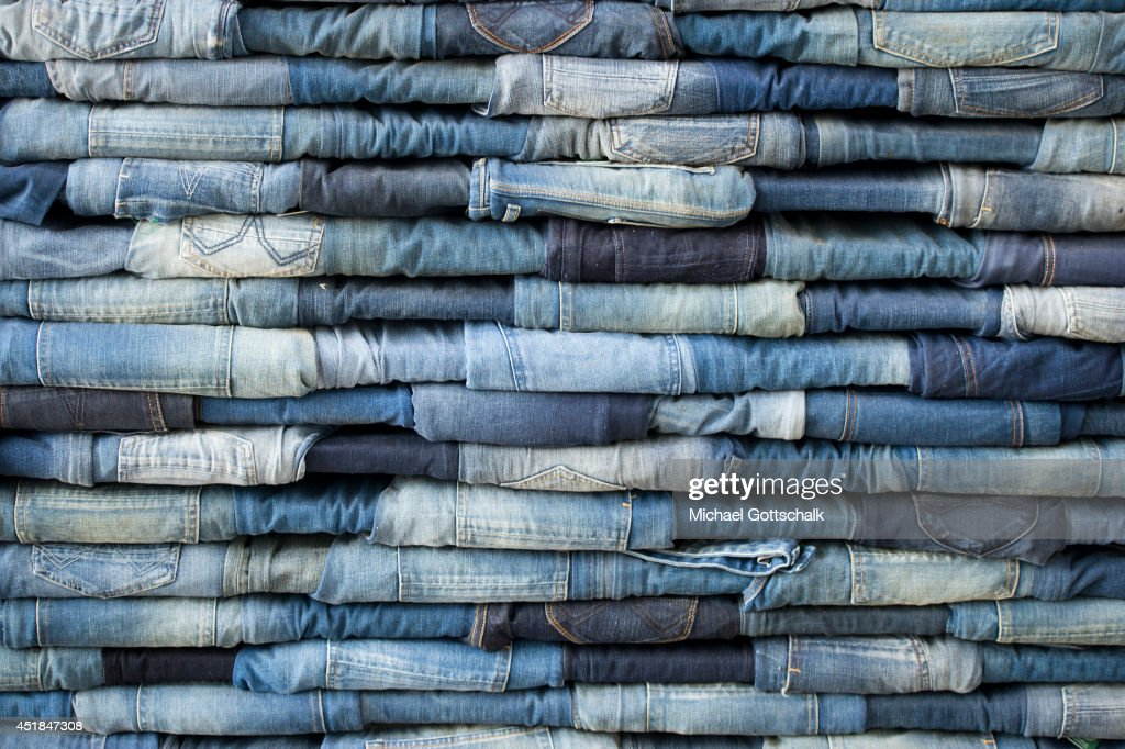 Jeans are piled in a booth of an exhibitor at the Bread and Butter trade show at the former Tempelhof airport on July 08, 2014 in Berlin, Germany.