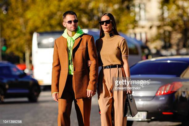 JeanSebastien Rocques wears a green hoodie sweater a brown blazer jacket Alice Barbier wears a turtleneck top beige pants outside Rochas during Paris...
