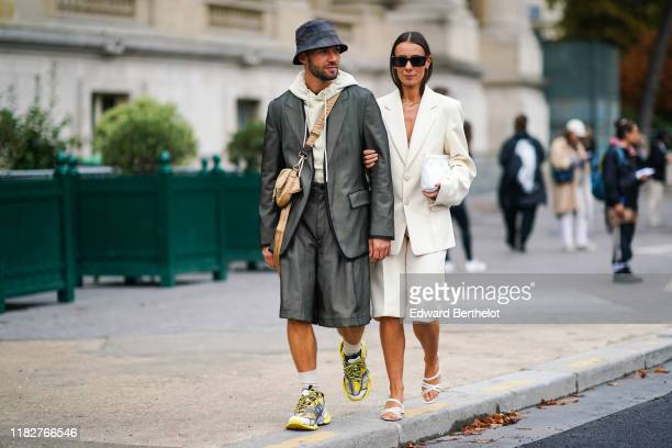 Jean-Sebastien Rocques wears a grey and navy blue checkered bob hat, a cream-color hooded sweatshirt, a lustrous grey jacket, assorted wide-legs...