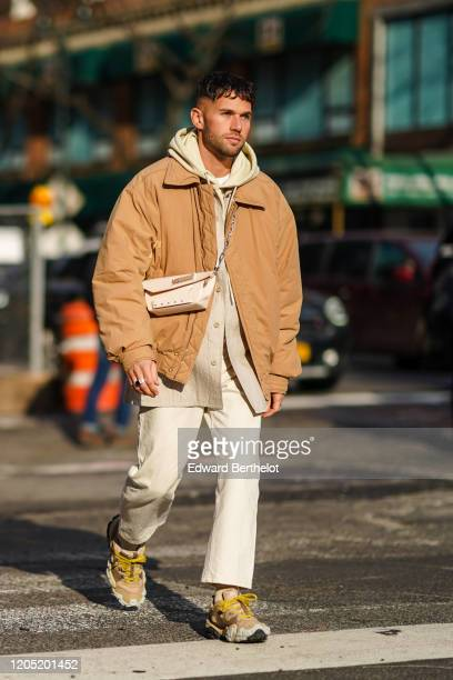 Jean-Sebastien Rocques wears a hoodie sweater, a bomber jacket, a crossbody bag, white pants, sneakers, outside Sies Marjan, during New York Fashion...