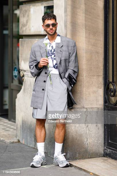 Jean-Sebastien Rocques wears sunglasses, a white shirt with navy blue prints, an oversized grey Prince of Wales long jacket, light grey shorts with...