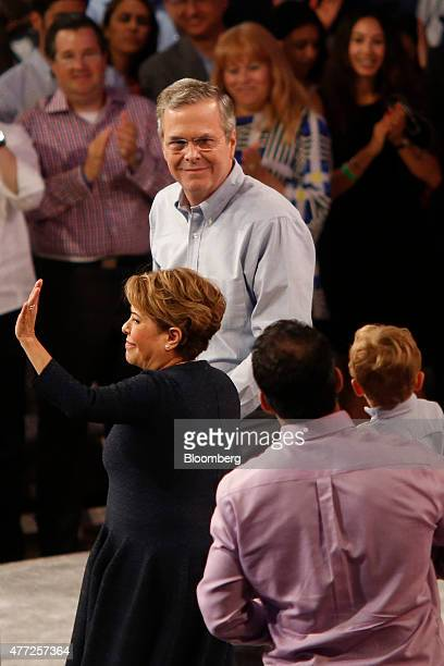 Jeb Bush former governor of Florida top stands on stage with his wife Columba Bush center and son George P Bush after announcing he will seek the...