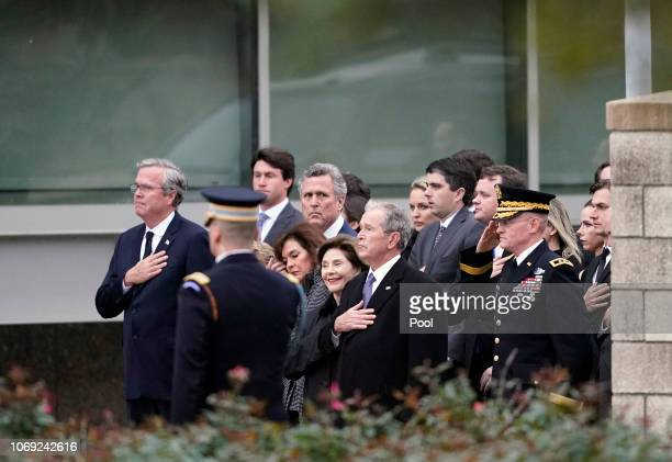 Jeb Bush, left, former President George W. Bush and Laura Bush and other family members watch as the flag-draped casket of former President George...