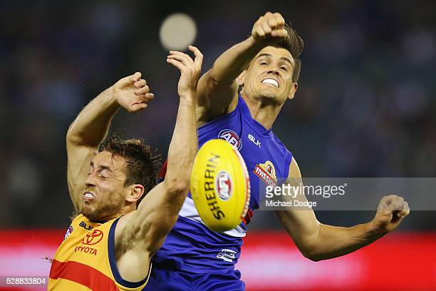 Jed Adcock of the Bulldogs punches the ball away from Matt Crouch of the Crows during the round seven AFL match between the Western Bulldogs and the...