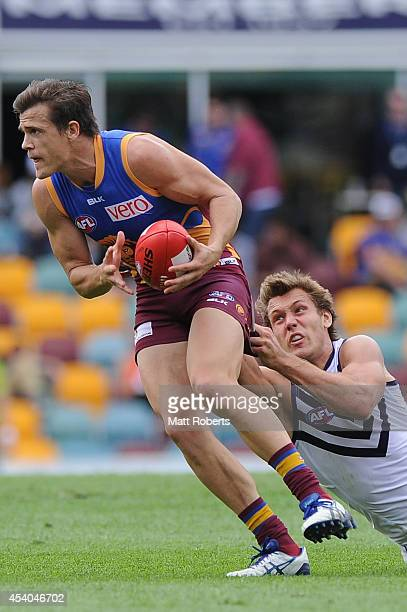 Jed Adcock of the Lions is tackled by Matt De Boer of the Dockers during the round 22 AFL match between the Brisbane Lions and the Fremantle Dockers...