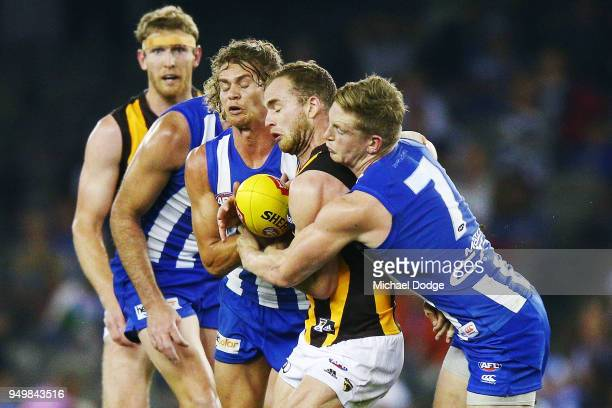 Jed Anderson of the Kangaroos and Jack Ziebell tackle Tom Mitchell of the Hawks during the round five AFL match between the North Melbourne Kangaroos...