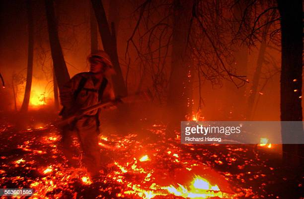 Jed Gaines with Camp Pendleton Fire Department rushes out of the brush as an entire neighborhood burns to the ground Wednesday evening along Hook...