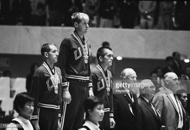Jed Graef of the United States celebrates on the podium his gold medal with compatriot silver medallist Gary Dilley and bronze medallist Bob Bennett...