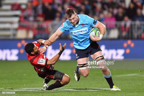 Jed Holloway of the Waratahs is tackled by Richie Mo'unga of the Crusaders during the round 12 Super Rugby match between the Crusaders and the...