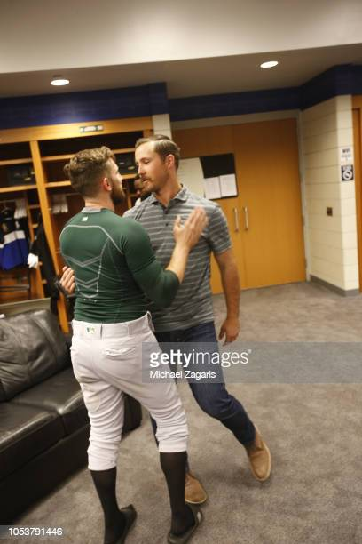 Jed Lowrie and Daniel Mengden of the Oakland Athletics embrace in the clubhouse following the game against the New York Yankees in the American...