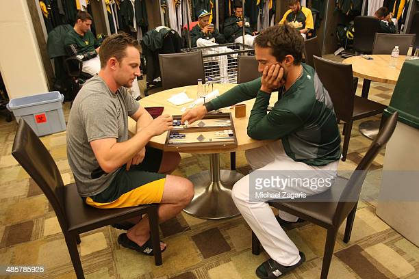 Jed Lowrie and Sam Fuld of the Oakland Athletics play backgammon in the clubhouse following game one of a double header against the Cleveland Indians...
