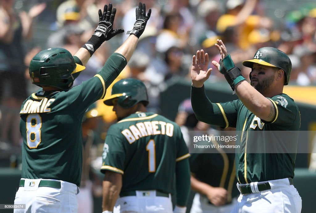Jed Lowrie #8 and Yonder Alonso #17 of the Oakland Athletics celebrates after they both scored against the Chicago White Sox in the bottom of the third inning at Oakland Alameda Coliseum on July 5, 2017 in Oakland, California.