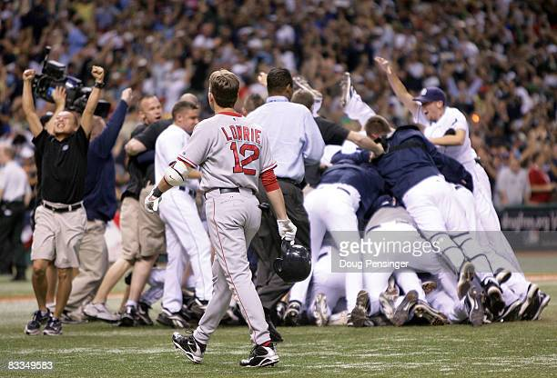 Jed Lowrie of the Boston Red Sox walks off the field as the Tampa Bay Rays celebrate winning game seven of the American League Championship Series...