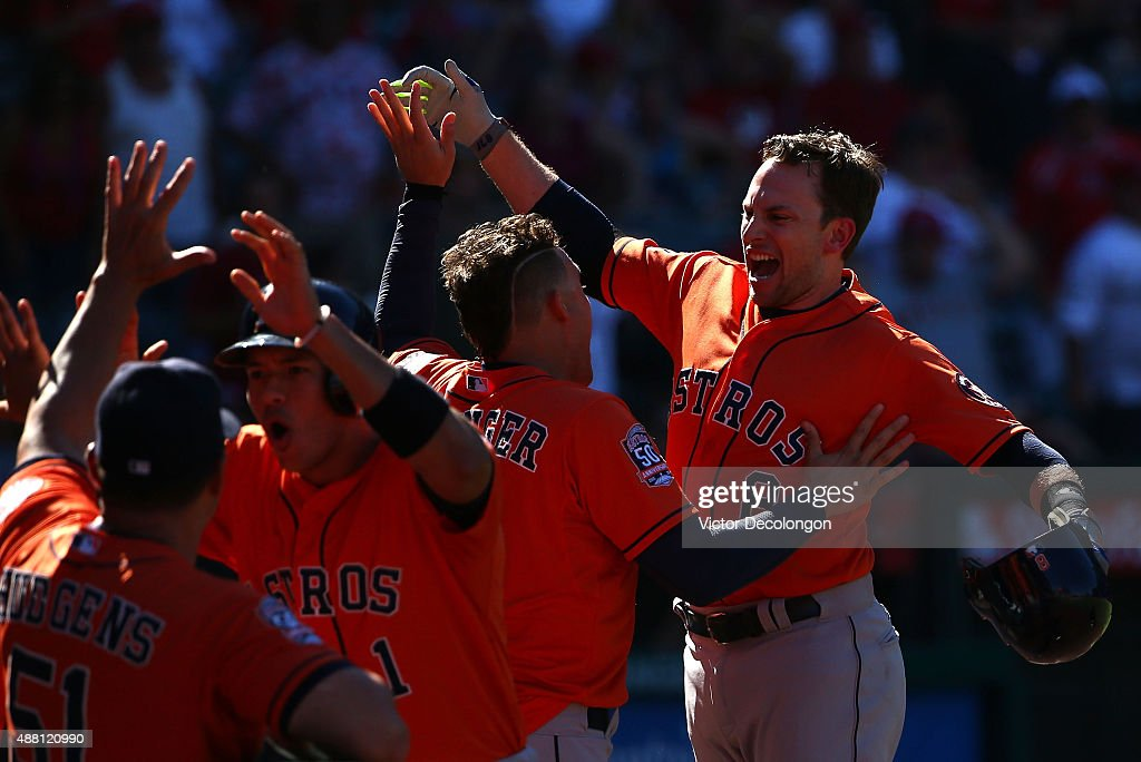 Jed Lowrie #8 of the Houston Astros celebrates with teammate George Springer #4 at the entrance to the dugout after Lowrie hit a three-run homerun in the ninth inning to take a 5-3 lead after trailing the Los Angeles Angels of Anaheim 3-0 going into the ninth during the MLB game at Angel Stadium of Anaheim on September 13, 2015 in Anaheim, California. The Astros defeated the Angels 5-3.