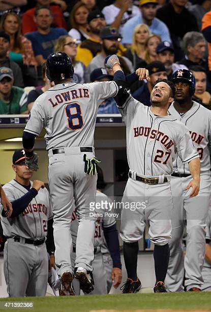 Jed Lowrie of the Houston Astros is congratulated by Jose Altuve after hitting a solo home run during the fourth inning of a baseball game against...