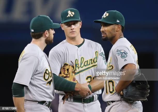 Jed Lowrie of the Oakland Athletics and Matt Chapman and Marcus Semien gather during a pitching change in the seventh inning during MLB game action...