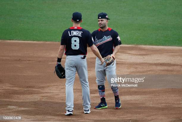 Jed Lowrie of the Oakland Athletics and the American League and Jose Altuve of the Houston Astros and the American League warm up before the 89th MLB...