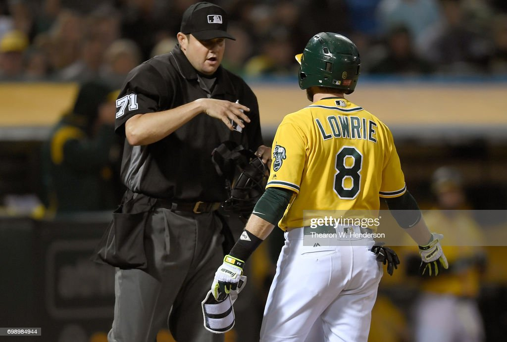 Jed Lowrie #8 of the Oakland Athletics argues with home plate umpire Jordan Baker #71 after Baker called Lowrie out on strikes against the Houston Astros in the bottom of the fifth inning at Oakland Alameda Coliseum on June 20, 2017 in Oakland, California.