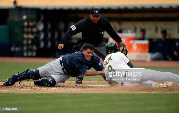 Jed Lowrie of the Oakland Athletics attempting to score on a fly ball to right field is tagged out at home plate by Henry Blanco of the Seattle...
