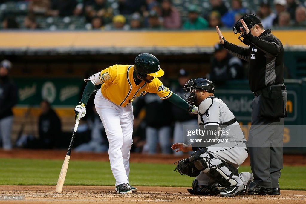 Jed Lowrie #8 of the Oakland Athletics checks on catcher Welington Castillo #21 of the Chicago White Sox after following through and hitting him on the helmet during the first inning at Oakland Alameda Coliseum on April 16, 2018 in Oakland, California.