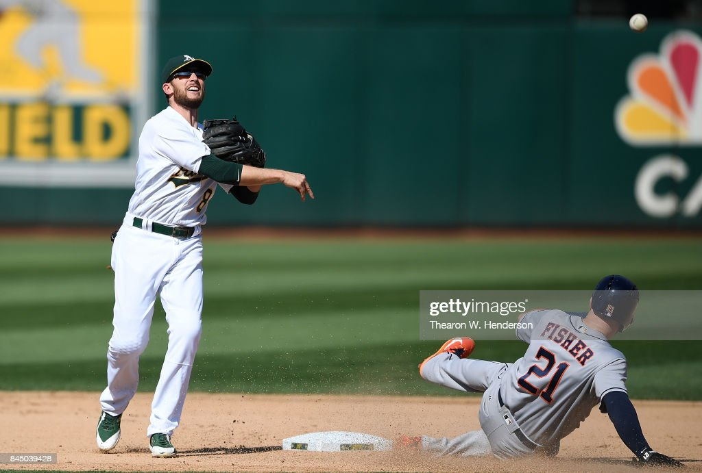Jed Lowrie #8 of the Oakland Athletics completes the double-play throwing over the top of Derek Fisher #21 of the Houston Astros in the top of the seventh inning during game one of a doubleheader at Oakland Alameda Coliseum on September 9, 2017 in Oakland, California.