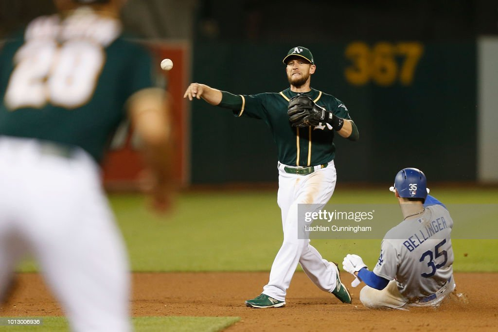Jed Lowrie #8 of the Oakland Athletics gets the out of Cody Bellinger #35 of the Los Angeles Dodgers at second base and throws to first base to make a double play in the seventh inning at Oakland Alameda Coliseum on August 7, 2018 in Oakland, California.