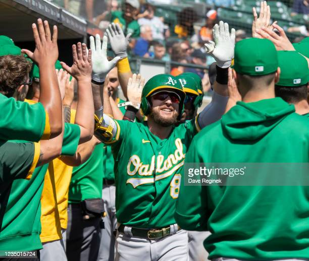 Jed Lowrie of the Oakland Athletics hits a two run home run against the Detroit Tigers in the first inning and celebrates with teammates in the...