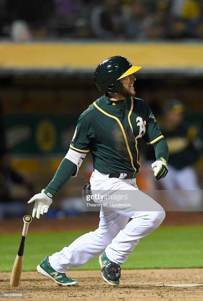 Jed Lowrie #8 of the Oakland Athletics hits a two-run rbi single against the Texas Rangers in the bottom of the fourth inning at the Oakland Alameda Coliseum on April 4, 2018 in Oakland, California.