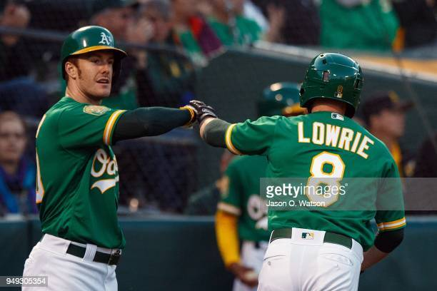 Jed Lowrie of the Oakland Athletics is congratulated by Mark Canha after scoring a run against the Boston Red Sox during the first inning at the...
