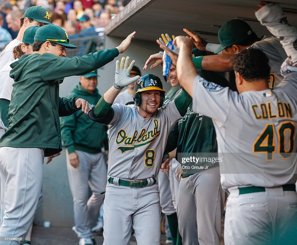 Jed Lowrie #8 of the Oakland Athletics is congratulated by teammates after hitting a home run in the fourth inning against the Seattle Mariners at Safeco Field on June 21, 2013 in Seattle, Washington.
