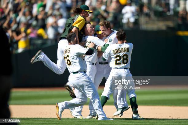 Jed Lowrie of the Oakland Athletics is congratulated by teammates after hitting a walk off single against the Houston Astros during the ninth inning...