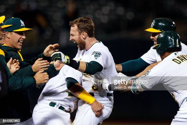 Jed Lowrie of the Oakland Athletics is congratulated by teammates after hitting a walk off single during the ninth inning against the Houston Astros...