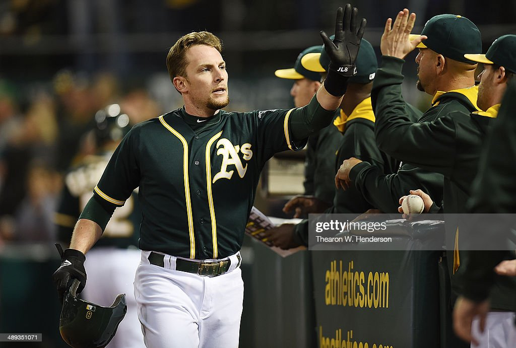 Jed Lowrie #8 of the Oakland Athletics is congratulated by teammates after he scored in the bottom of the ninth inning against the Washington Nationals at O.co Coliseum on May 10, 2014 in Oakland, California. Lowrie's run tied the score 3-3.