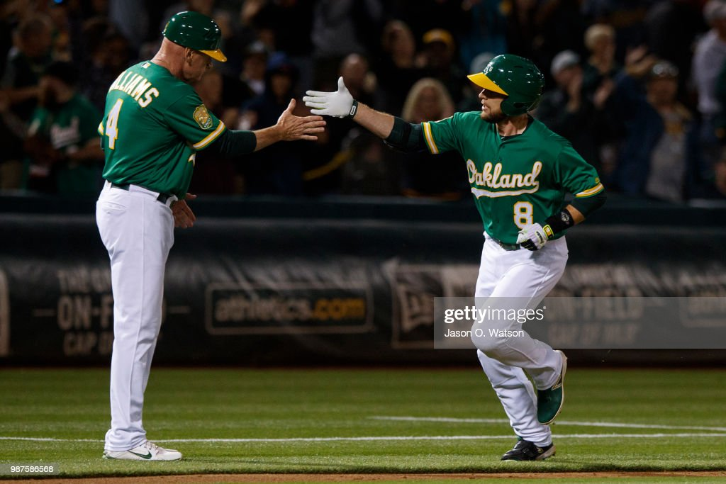 Jed Lowrie #8 of the Oakland Athletics is congratulated by third base coach Matt Williams #4 after hitting a home run against the Cleveland Indians during the eighth inning at the Oakland Coliseum on June 29, 2018 in Oakland, California. The Oakland Athletics defeated the Cleveland Indians 3-1.
