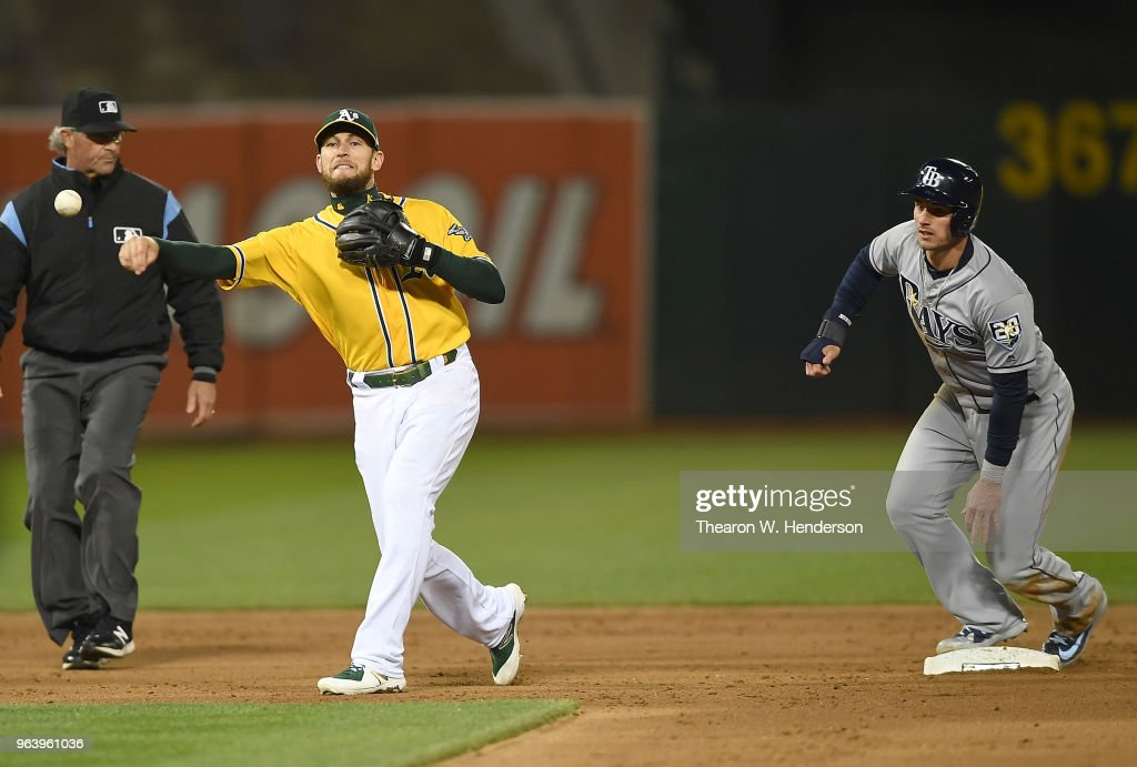 Jed Lowrie #8 of the Oakland Athletics looks to throw to first base to complete the double play after stepping on second base to get Daniel Robertson #28 of the Tampa Bay Rays in the top of the six inning at the Oakland Alameda Coliseum on May 30, 2018 in Oakland, California.