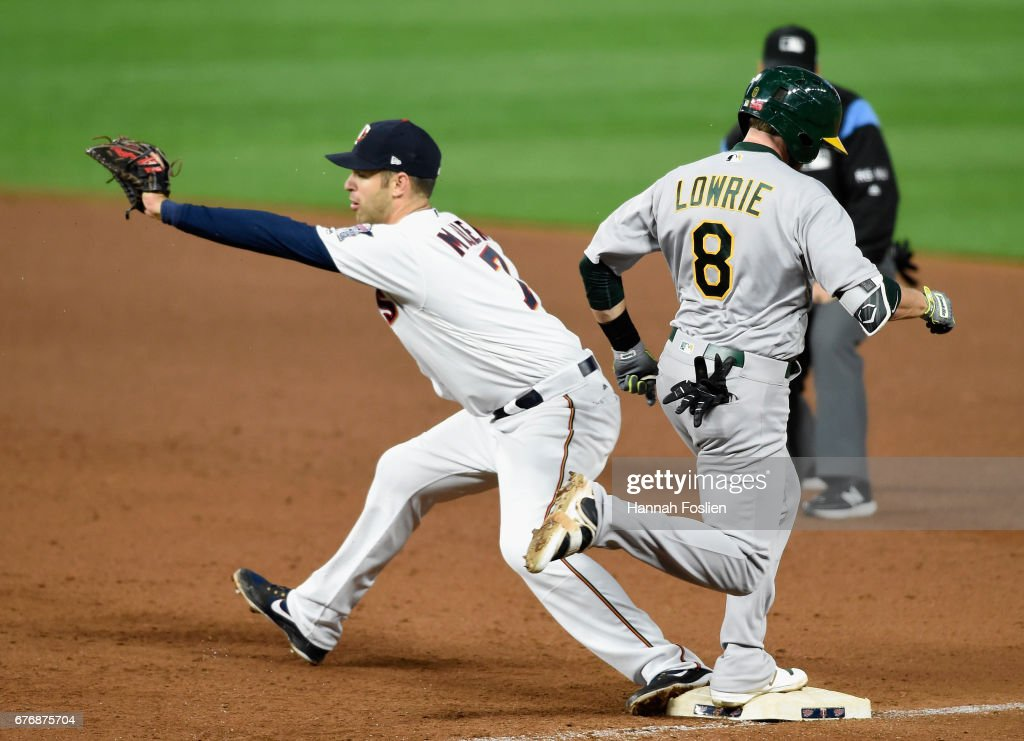 Jed Lowrie #8 of the Oakland Athletics reaches first base safely as Joe Mauer #7 of the Minnesota Twins takes the throw during the sixth inning of the game on May 2, 2017 at Target Field in Minneapolis, Minnesota. The Twins defeated the Athletics 9-1.
