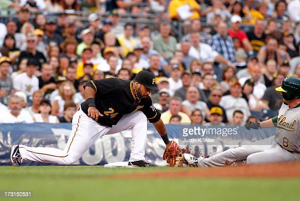 Jed Lowrie of the Oakland Athletics slides in safe in the fourth inning against Pedro Alvarez of the Pittsburgh Pirates during the game on July 8...