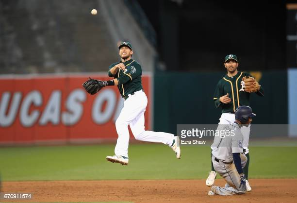 Jed Lowrie of the Oakland Athletics turns an unassisted double play as Jarrod Dyson of the Seattle Mariners slides in to second base on a ball hit by...