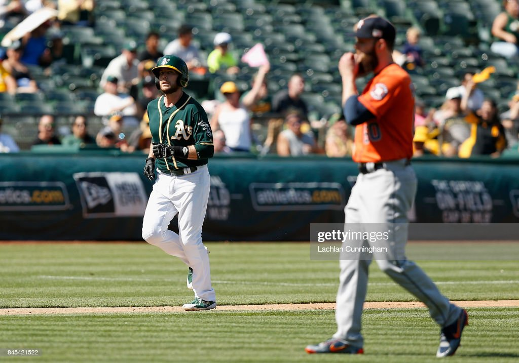 Jed Lowrie #8 of the Oakland Athletics walks to home plate to score after pitcher Dallas Keuchel (right) #60 of the Houston Astros walked Matt Chapman #26 of the Oakland Athletics with bases loaded in the sixth inning at Oakland Alameda Coliseum on September 10, 2017 in Oakland, California.