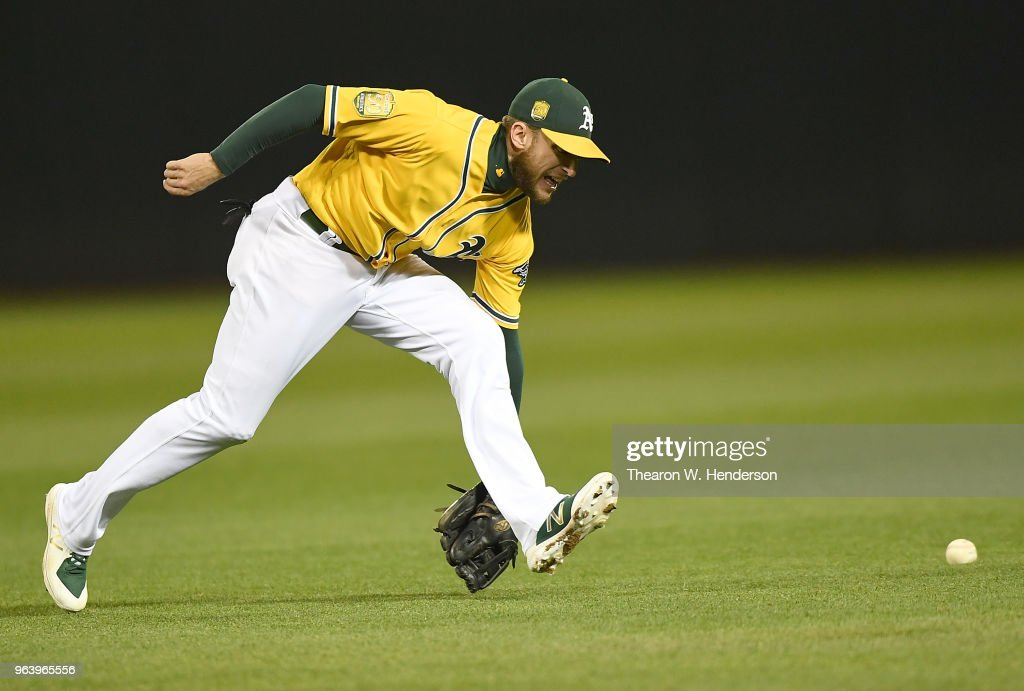Jed Lowrie #8 of the Oakland Athletics watches the ball go past him for a base hit off the bat of Daniel Robertson #28 of the Tampa Bay Rays in the top of the eighth inning at the Oakland Alameda Coliseum on May 30, 2018 in Oakland, California. The Rays won the game 6-0.