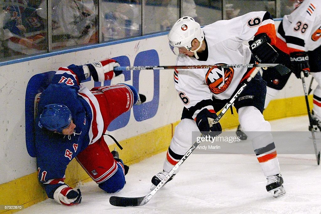 Jed Ortmeyer #41 of the New York Rangers goes hard into the boards after being checked by Darius Kasparaitis #6 of the New York Islanders on April 11, 2006 at Madison Square Garden in New York City.